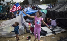 A migrant girls waves a U.S. flag while on a shelter in Tijuana, Mexico - Photo: Rodrigo Abed/AP